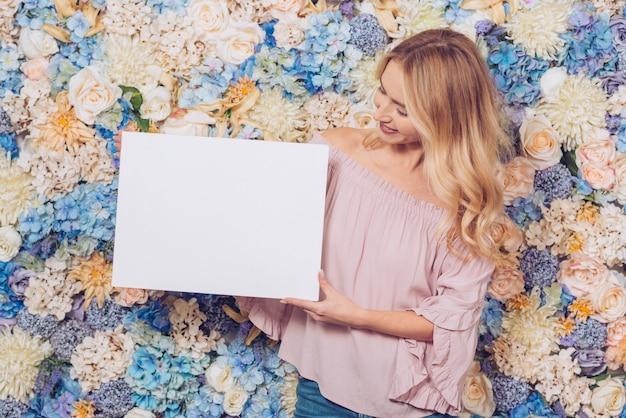 Donna in piedi con foglio di carta bianca
