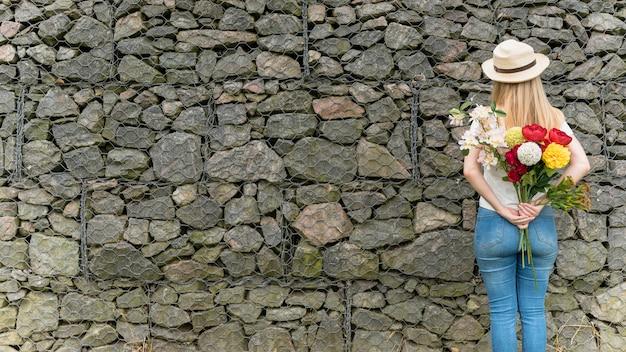 Donna in piedi con i fiori alle spalle