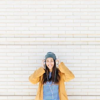 Donna in piedi contro il muro di mattoni godendo la musica d'ascolto con gli occhi chiusi