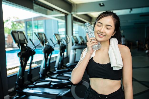 Donna in piedi e rilassarsi dopo l'esercizio fisico, tenendo una bottiglia d'acqua per toccare il viso.