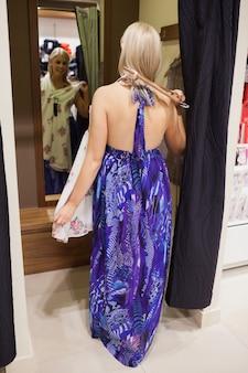 Donna in piedi nello spogliatoio cercando vestiti
