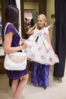 Donna in piedi nello spogliatoio di una boutique con un amico