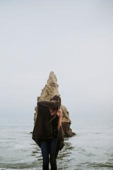 Donna in piedi sulla spiaggia che copre il viso