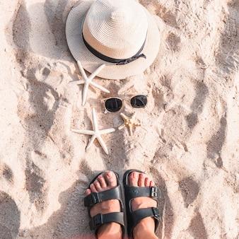 Donna in piedi sulla spiaggia di sabbia con stelle marine