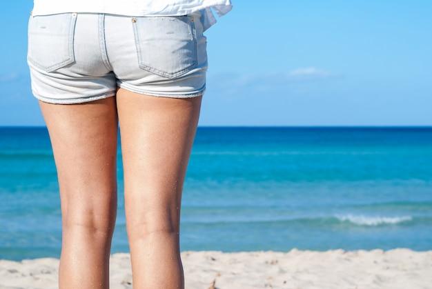 Donna in piedi sulla spiaggia di sabbia. dettaglio del primo piano delle gambe