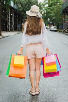 Donna in piedi sulla strada con borse della spesa