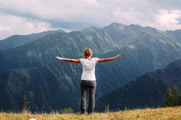Donna in piedi sulle montagne