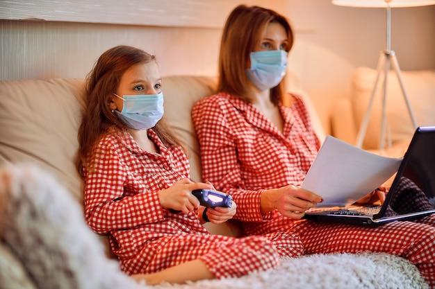 Donna in pigiama con il taccuino e le carte che lavorano da casa indossando maschera protettiva mentre sua figlia gioca con i videogiochi