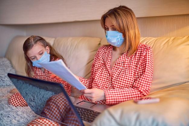 Donna in pigiama con il taccuino e le carte che lavorano da casa indossando una maschera protettiva mentre sua figlia gioca ai videogiochi