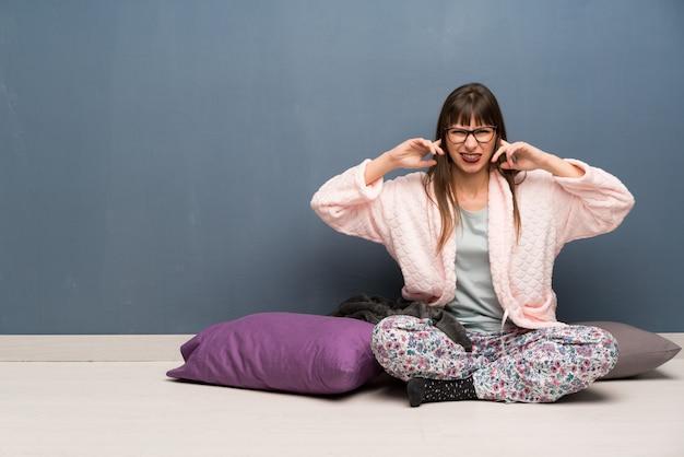Donna in pigiama sul pavimento frustrato e che copre le orecchie con le mani