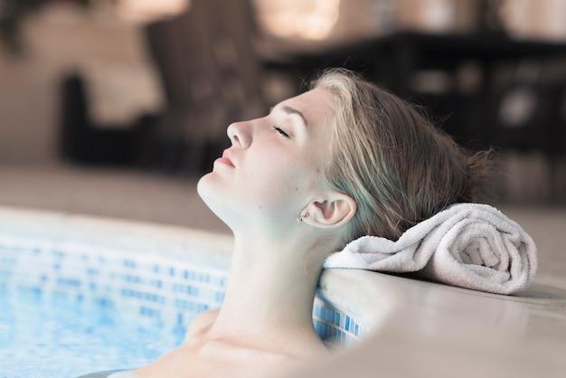 Donna in piscina che si appoggia la testa sul bordo del tovagliolo arrotolato