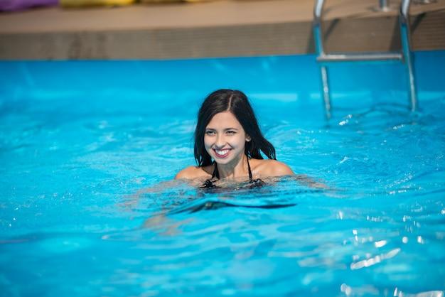 Donna in piscina con acqua turchese al sole presso il resort