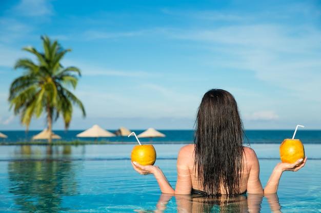 Donna in piscina con cocktail