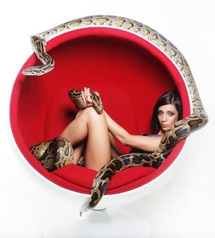 Donna in pitone holdung rosso della sedia