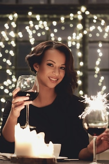Donna in ristorante che tiene un bicchiere di vino