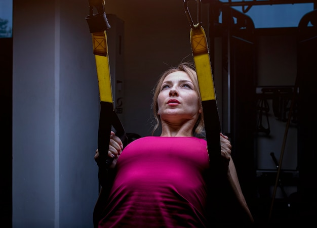 Donna in rosa che fa addestramento posteriore con la macchina posteriore di estensione in una palestra.
