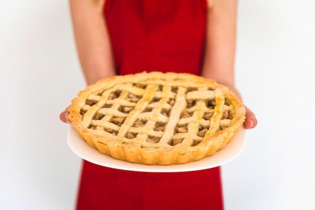 Donna in rosso tenendo il piatto con torta di mele
