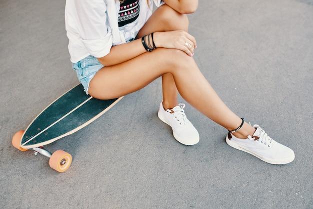 Donna in scarpe da tennis che guidano pattino all'aperto sulla superficie dell'asfalto.