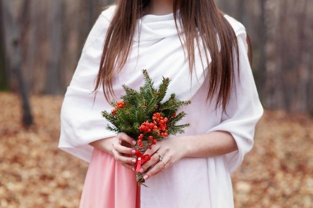 Donna in scialle bianco detiene bouquet di bacche rosse e abete