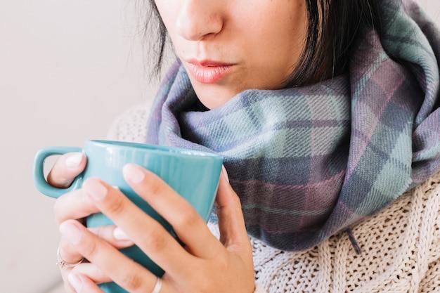 Donna in sciarpa che soffia sulla tazza