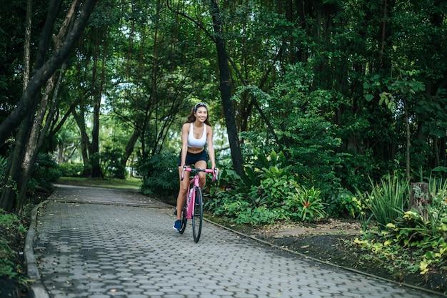 Donna in sella a una bici da strada nel parco. ritratto di giovane donna bella sulla bici rosa.