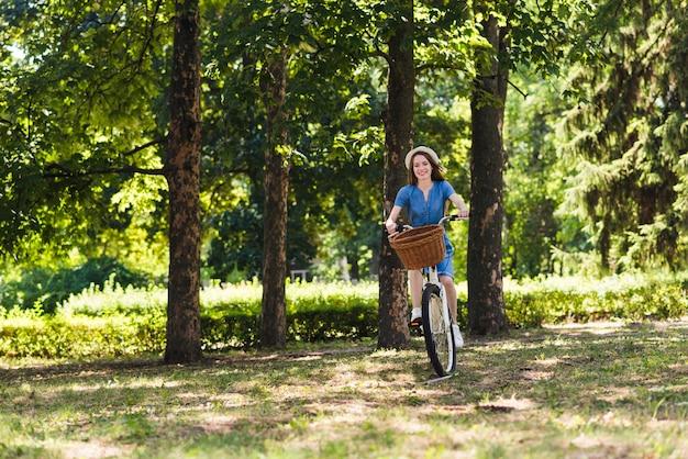 Donna in sella a una bici sul sentiero forestale