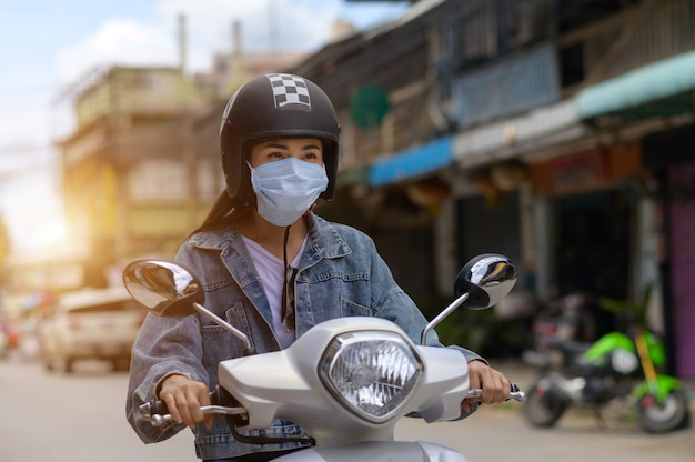 Donna in sella a una moto che indossa una maschera in città