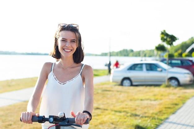 Donna in sella a uno scooter e guardando la telecamera
