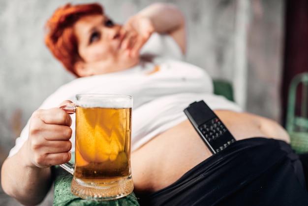 Donna in sovrappeso con un bicchiere di birra in mano, obesità