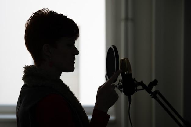 Donna in studio di registrazione che registra cantando e parlando per l'elaborazione e l'utilizzo per film e video