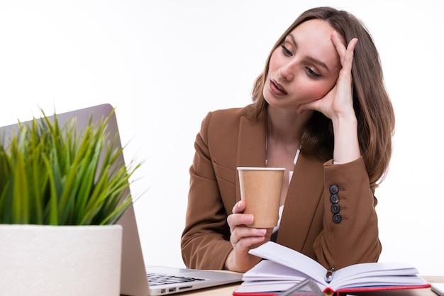Donna in tailleur e camicia bianca che beve caffè