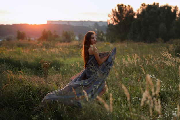 Donna in tessuto trasparente grigio al tramonto in estate nel campo