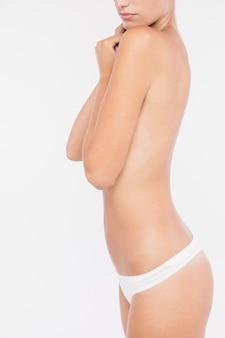 Donna in topless che copre il petto con le braccia