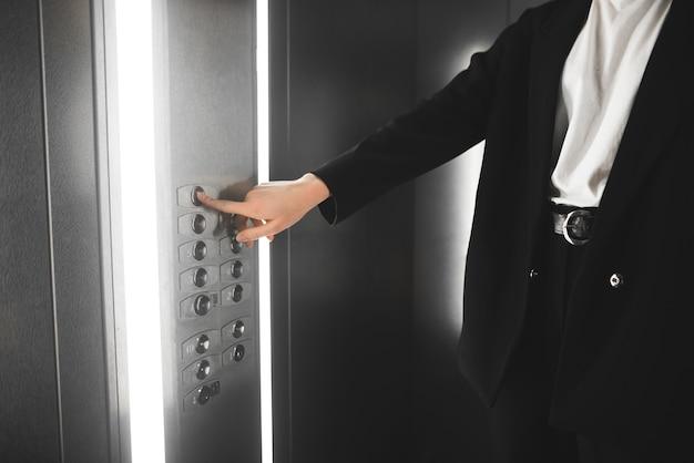 Donna in tuta che spinge il pulsante nell'ascensore.