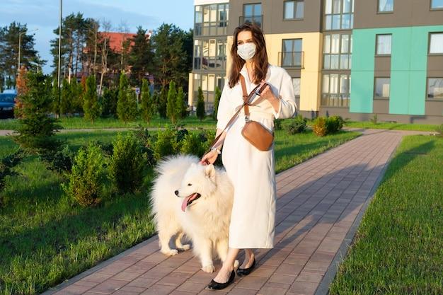Donna in un abito bianco e una maschera sul viso che cammina con un cane
