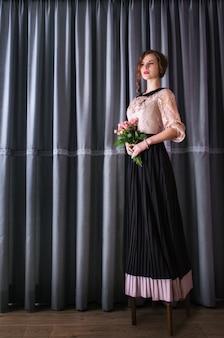 Donna in un abito lungo in possesso di un mazzo di rose
