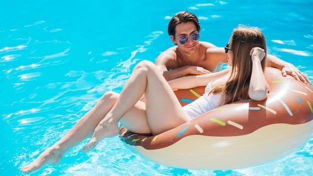 Donna in un anello di nuotata ciambella parlando con l'uomo