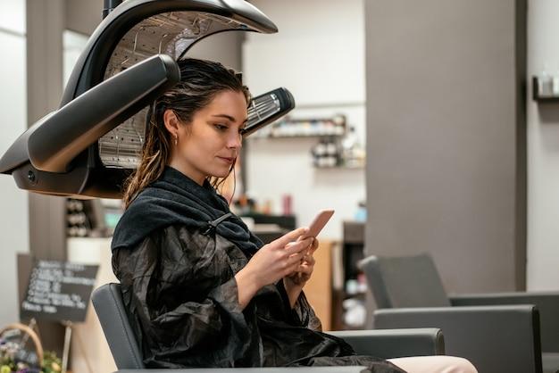 Donna in un asciugacapelli a infrarossi professionale parrucchiere