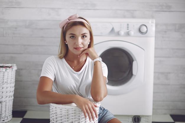Donna in un bagno vicino a lavaggio mashine