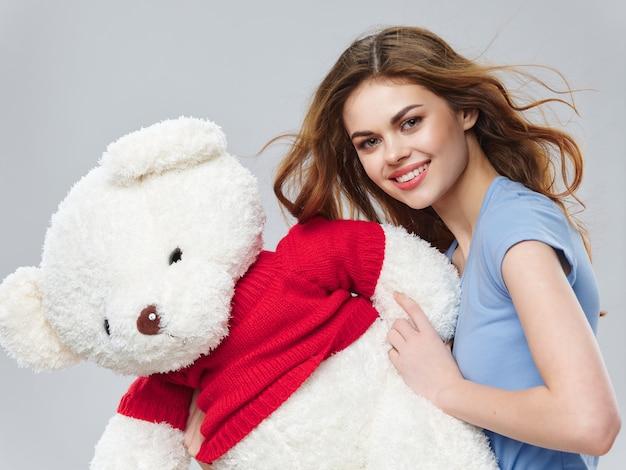 Donna in un bel vestito con fiori l'8 marzo, regali fiori sfondo chiaro san valentino