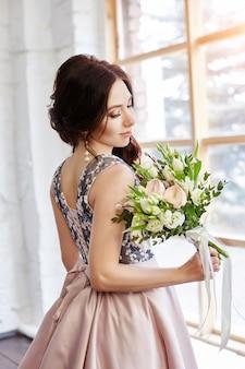Donna in un bellissimo vestito e un grande mazzo