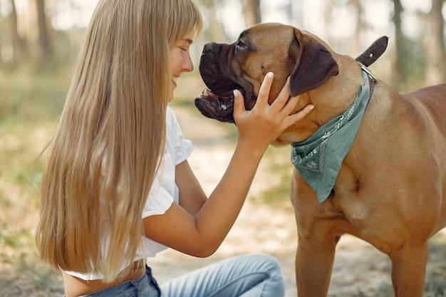 Donna in un bosco estivo a giocare con il cane