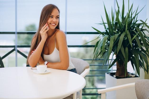 Donna in un caffè che beve tè e utilizzando il telefono