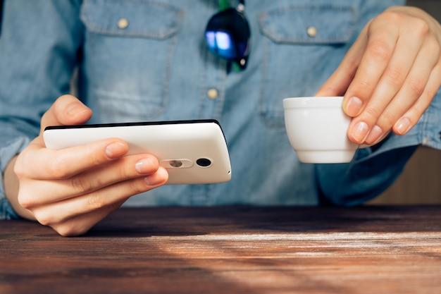 Donna in un caffè in possesso di un telefono cellulare e bere caffè