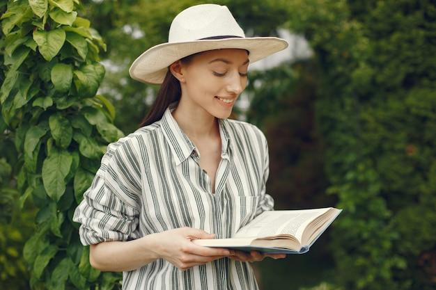 Donna in un cappello con un libro in un giardino