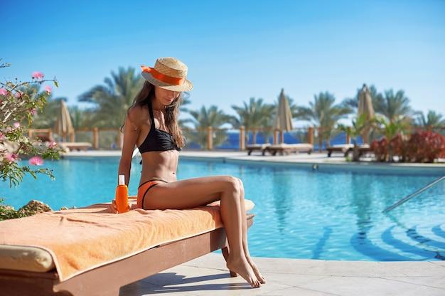 Donna in un cappello di paglia rilassante su un divano vicino a una piscina estiva di lusso con crema solare
