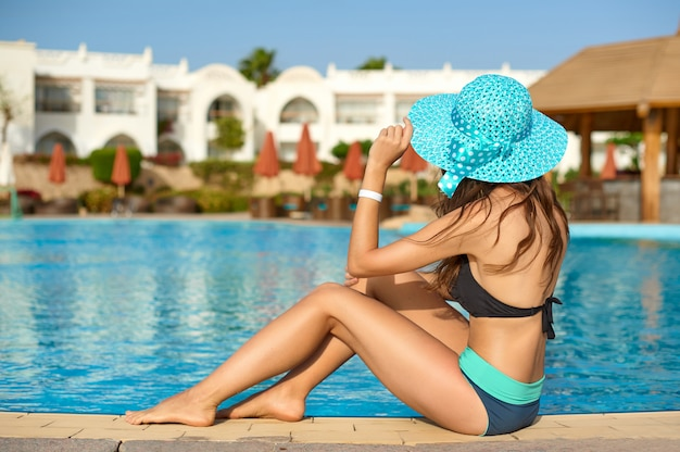 Donna in un cappello di paglia rilassante su una sdraio vicino a una piscina estiva di lusso in hotel, tempo di concetto di viaggiare