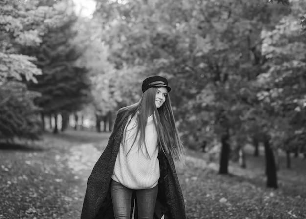 Donna in un cappello in un parco di autunno