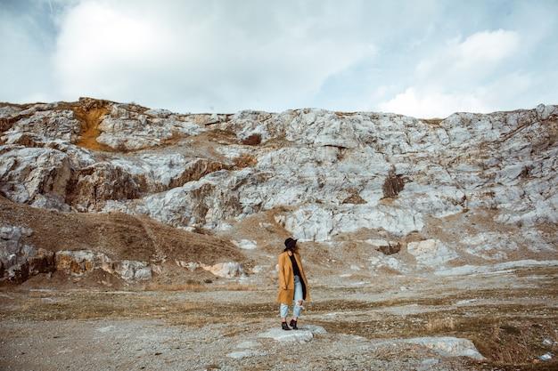 Donna in un cappotto che sta nelle montagne rocciose un giorno di autunno