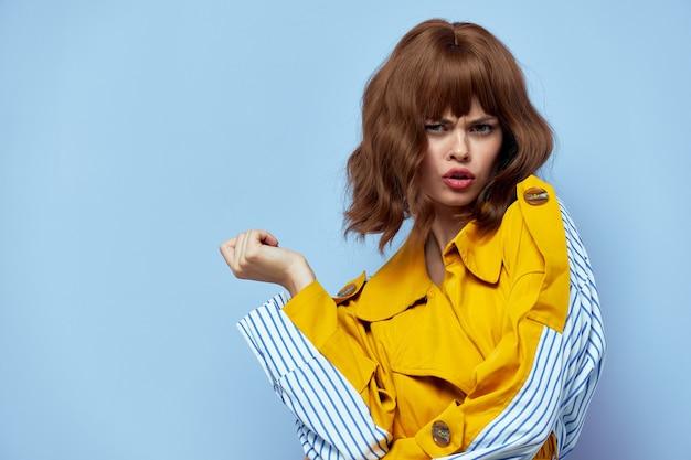 Donna in un cappotto giallo gesti con le mani sul blu